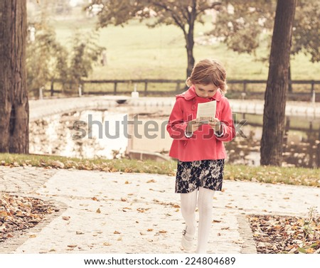 young thoughtful girl walking and reading in park on a fall day, vintage picture - stock photo