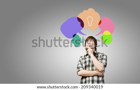 Young thoughtful man and colorful speech bubbles above - stock photo