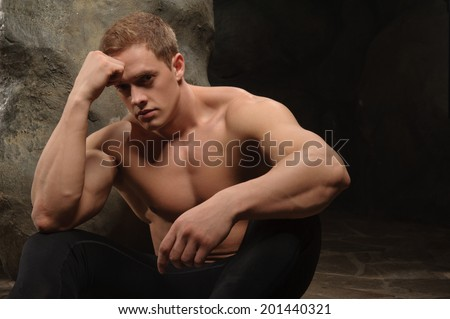 Young thoughtful muscular man sitting by the rock on dark background