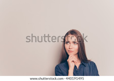 Young thoughtful pretty girl isolated on gray background - stock photo