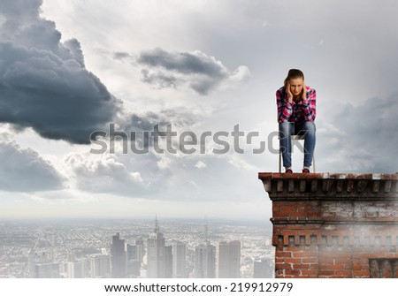 Young thoughtful woman in casual sitting in chair - stock photo