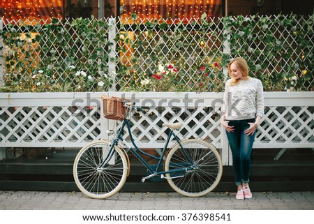 Young Thoughtful Woman on a Vintage Bicycle at the City Street Standing near Street Cafe with Flower Wall. Selective focus. - stock photo