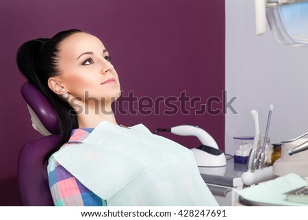 Young thoughtful woman patient sitting in chair waiting for dentist ready for a checkup and looking up into the air. Beautiful girl in checkered shirt in dental clinic - stock photo