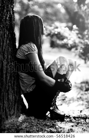 Young thoughtful woman sitting in park. Black and white. - stock photo