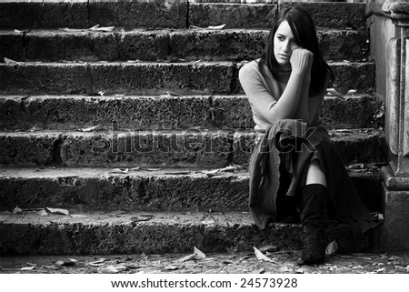 Young thoughtful woman sitting in stone stairs. - stock photo