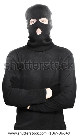 Young thug turned criminal posing with his arms folded wearing a black outfit with hooded mask to conceal his identity, isolated on a white studio background - stock photo