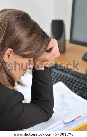 Young tired and depressed business person (woman) sitting at table with computer and documents - stock photo