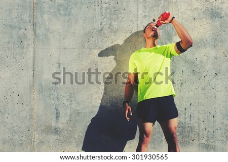 Young tired athlete refreshing with energy drink while standing against cement wall background with copy space area for your text message or content, male runner resting after exercise outdoors - stock photo