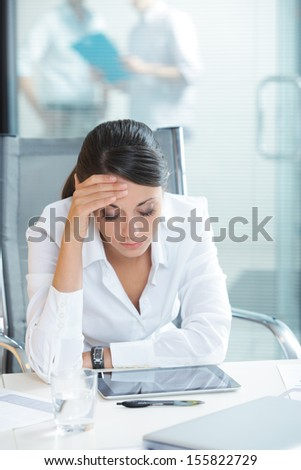 Young tired business woman with headache sitting  in workplace