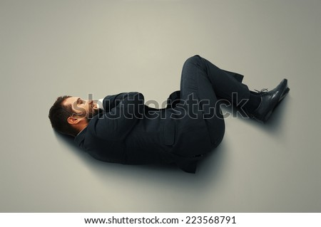 young tired businessman in suit  sleeping on the grey floor