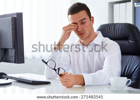 Young tired businessman rubbing his eye - stock photo