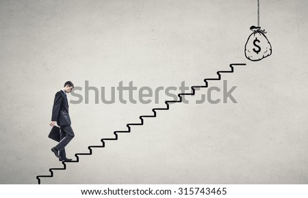 Young tired businessman walking up on staircase representing wealth concept