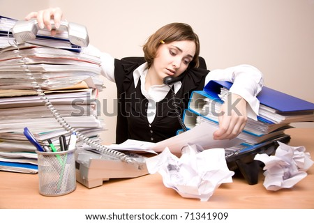Young tired businesswoman with tons of documents calling phone - stock photo