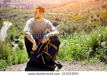 Young tired hiker with backpack sitting on the mountain top while resting after active walk, active traveler man hiking in beautiful nature in sunny day, male tourist taking break after long hike way - stock photo