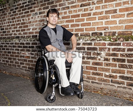 young to middle age man in wheelchair with determined expression - stock photo