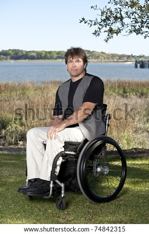 young to middle-age man with determined look in wheelchair - stock photo