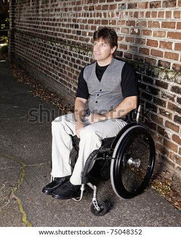young to middle aged man in wheelchair with determined look - stock photo
