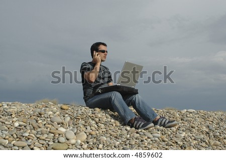 young to the cellular one and with the computer in top of the legs, to the outdoors... - stock photo