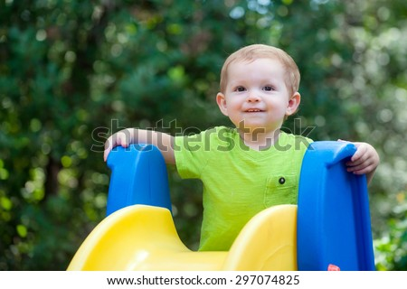 Young toddler boy child playing on slide - stock photo