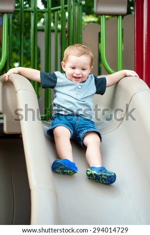 Young toddler boy child playing on slide at playground outdoors during summer - stock photo