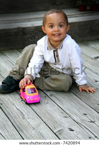 Young toddler boy playing with car - stock photo