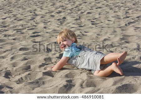 young toddler child boy falling and rolling over in sand