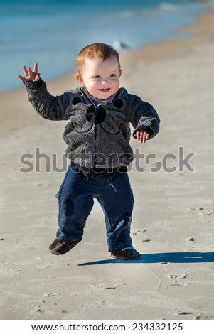 Young toddler walking and playing on beach  - stock photo