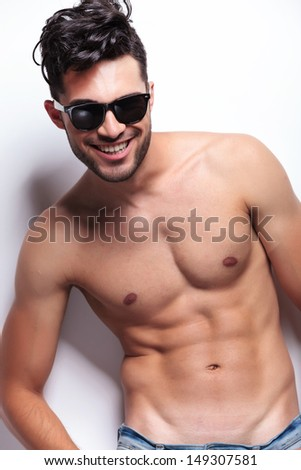 young topless man looking at the camera with a big smile on his face. on light gray background