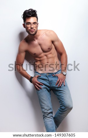 young topless man standing with his thumbs in the loops of his jeans and looking at the camera. on light gray background - stock photo