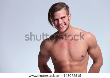 young topless man with lean body showing a big smile and revealing braces. on gray background - stock photo