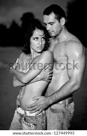 Young topless nude lovers on the Beach - stock photo