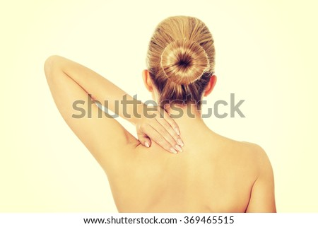 Young topless woman with back pain - stock photo