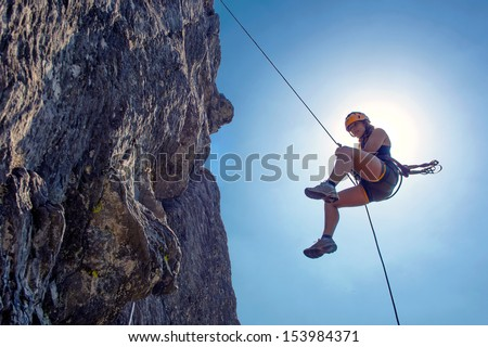 Young, tough, woman, abseiling from a steep rock, just in front of the sun - stock photo