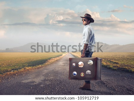 Young tourist carrying a suitcase on a country road - stock photo