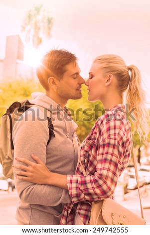 Young tourist couple about to kiss on a sunny day in the city - stock photo