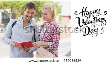 Young tourist couple consulting the guide book against happy valentines day - stock photo