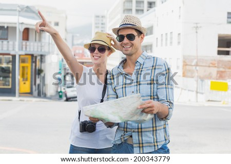 Young tourist couple consulting the map and pointing on a sunny day in the city - stock photo