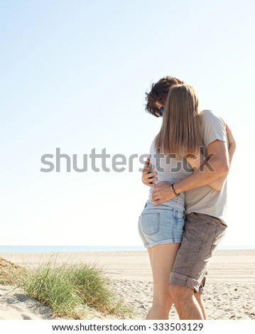 Young tourist couple hugging and kissing on a sunny white sand beach on holiday, enjoying together a vacation on a coastal destination, exterior. Travel and romance lifestyle, recreation outdoors.