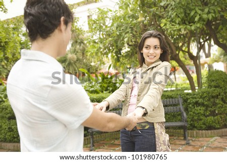 Young tourist couple playfully holding hands in a town's square while on vacations. - stock photo