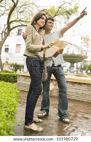 Young tourist couple sightseeing using a map. - stock photo