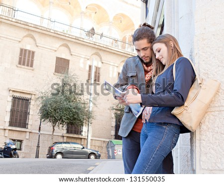 Young tourist couple standing together in a destination city holding and looking at a street map while on vacation. - stock photo