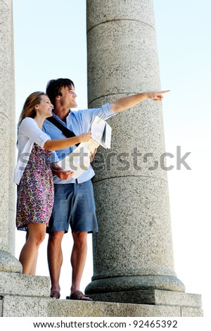 young tourist couple use their map to determine direction and point in the way they wish to go - stock photo
