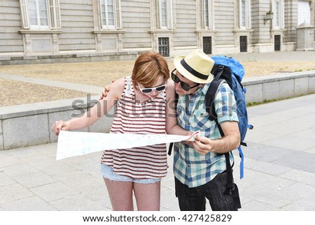 young tourist couple visiting Madrid in Spain lost and confused loosing orientation with boyfriend carrying travel backpack and girl holding city map in holiday trip and vacation concept - stock photo