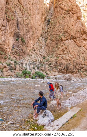 Young tourist enjoying river in Todgha Gorge, Morocco - stock photo