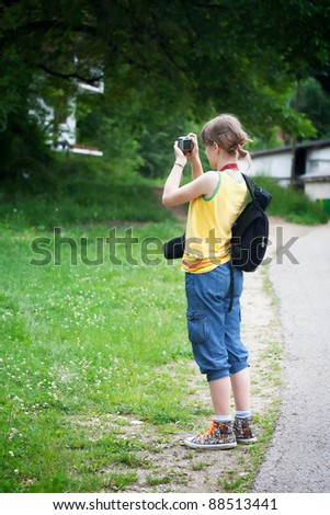 young tourist girl with camera taking landscape picture - stock photo