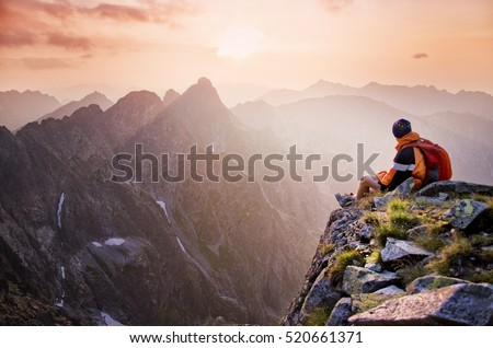 Young tourist, hiker with backpack siting on the top of the hill of mountains and looking at beautiful summer sunset