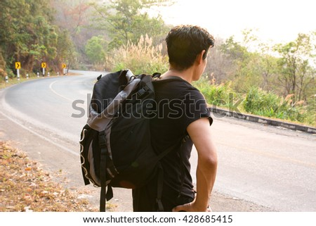 Young tourist man on the road,Man hitchhiking,Man  travel,Journey,Alone,Blurry portrait - stock photo