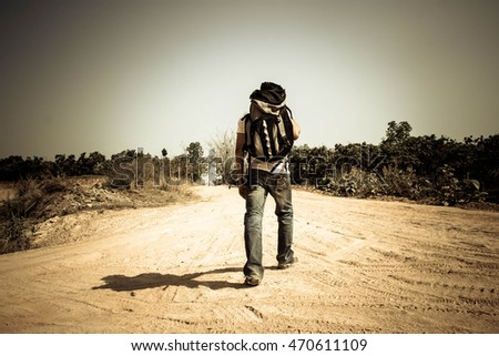Young tourist man walking on the road,Man hitchhiking,Man  travel,Journey,Alone