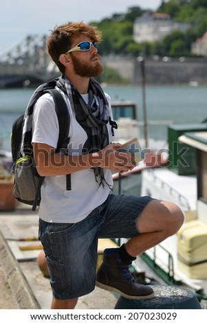 young tourist man with backpack and city map