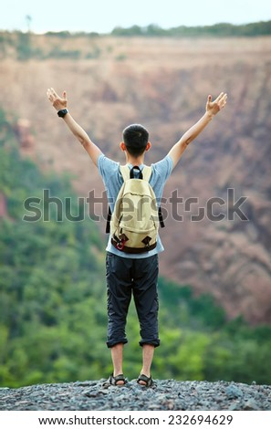 Young tourist man with backpack standing with raised hands on rocky cliff - stock photo